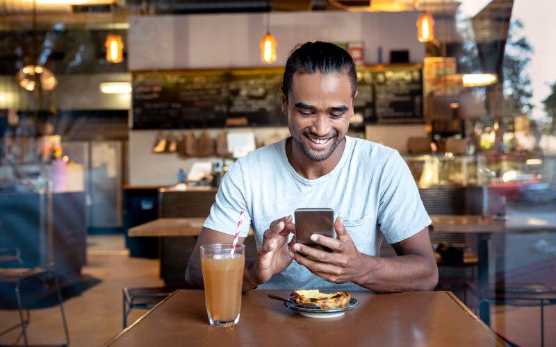 A young man sitting in a cafe, smiling while interacting with his smartphone